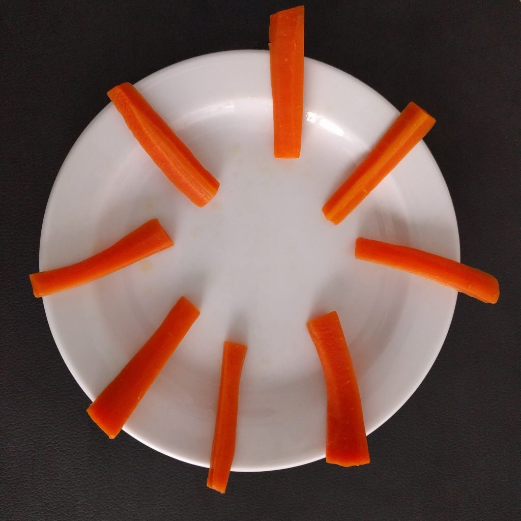 Gulerodsstave placeret på en hvid tallerken