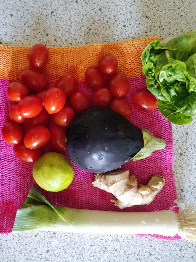 Forskellige grøntsager ligger på en pink og orange strikket karklud.