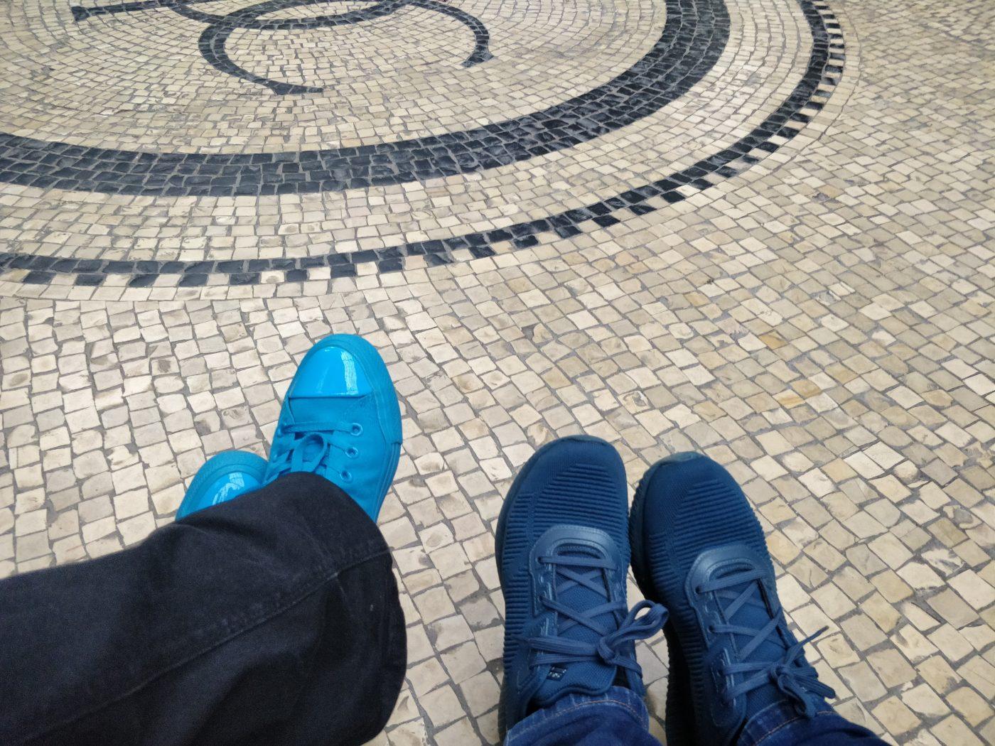 To personer sidder på en bænk på Glyptoteket, begge iført blå sko.