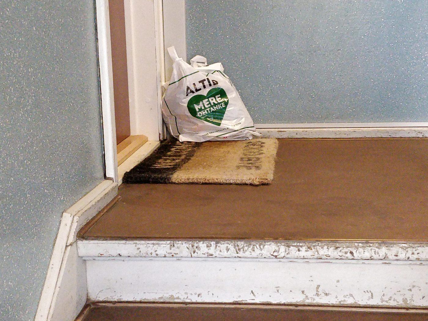 """En plastikpose med affald i trappeopgangen. På posen står der """"Altid mere omtanke"""""""