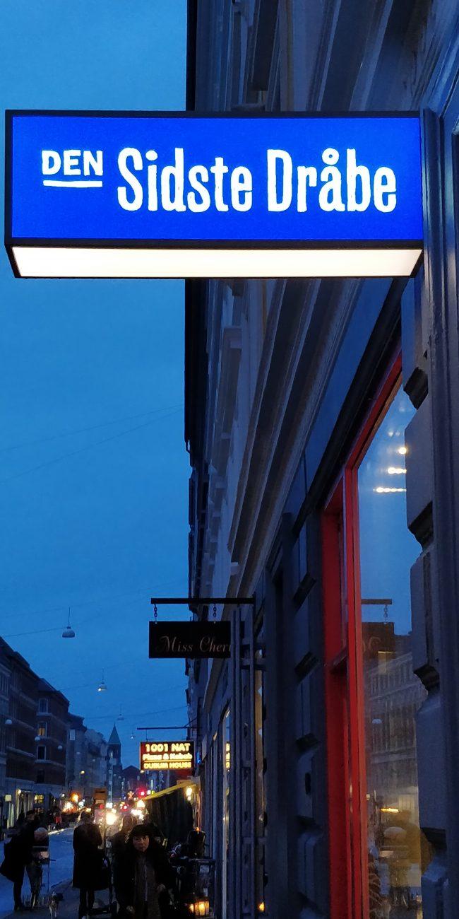 """Blå aftenhimmel over Istedgade, Købehavn. Et skilt med teksten """"Den sidste dråbe""""."""