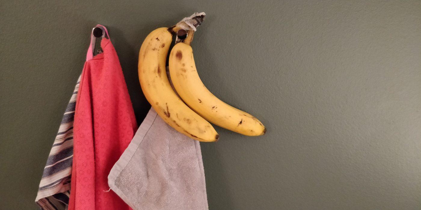 Et par knager, hvor der hænger et håndklæde, et viskestykke samt to bananer.