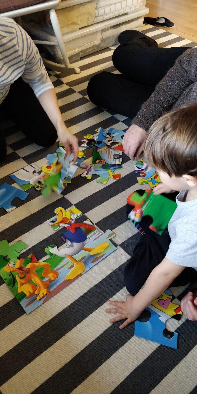 To voksne og et barn lægger et puslespil på gulvet.