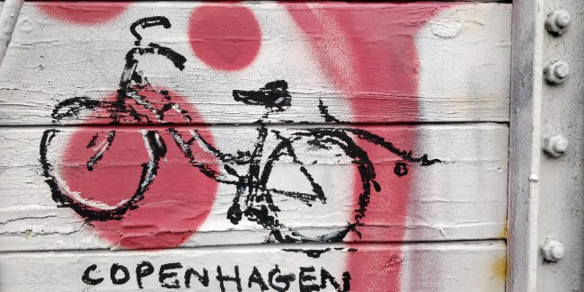 Street art: a black bicycle on a white and pink background, Copenhagen.