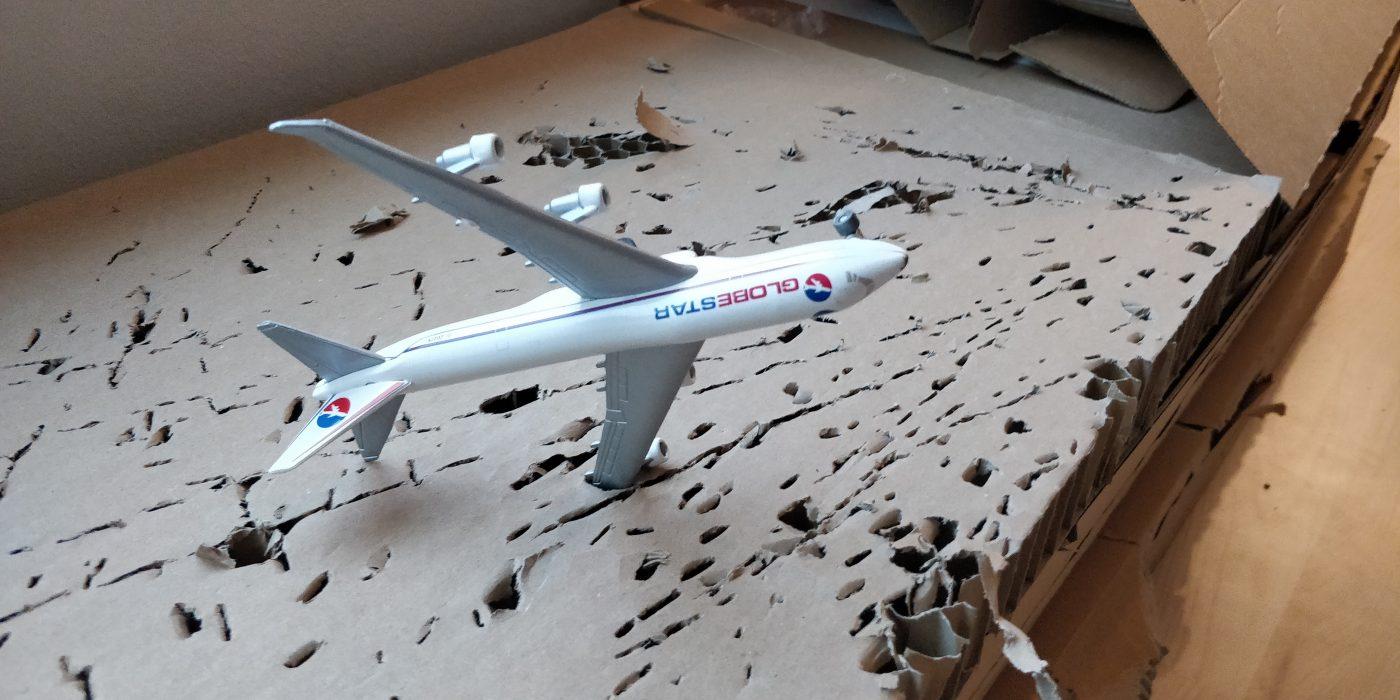 Kraftigt bølgepap, der er perforeret af vingespidsen af et modelfly.