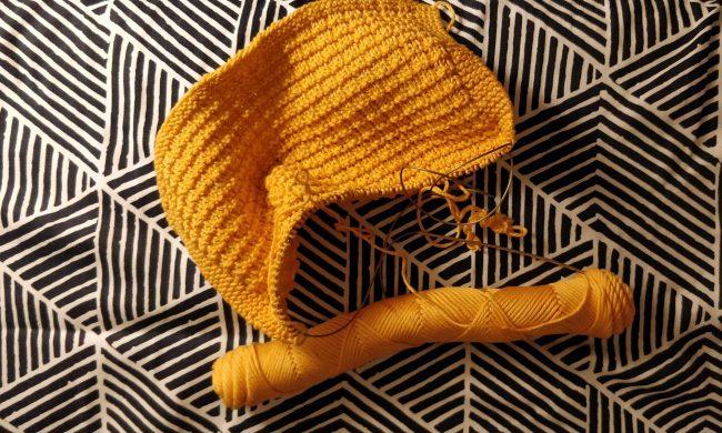 En halvfærdig, orange, strikket karklud.