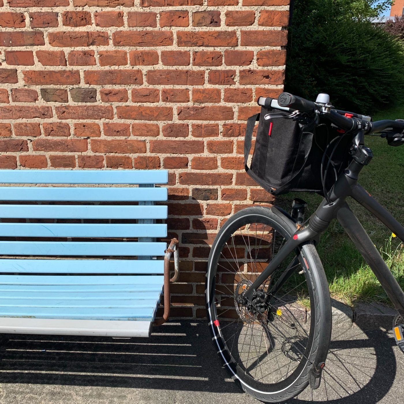 Blå bænk, sort cykel, røde mursten