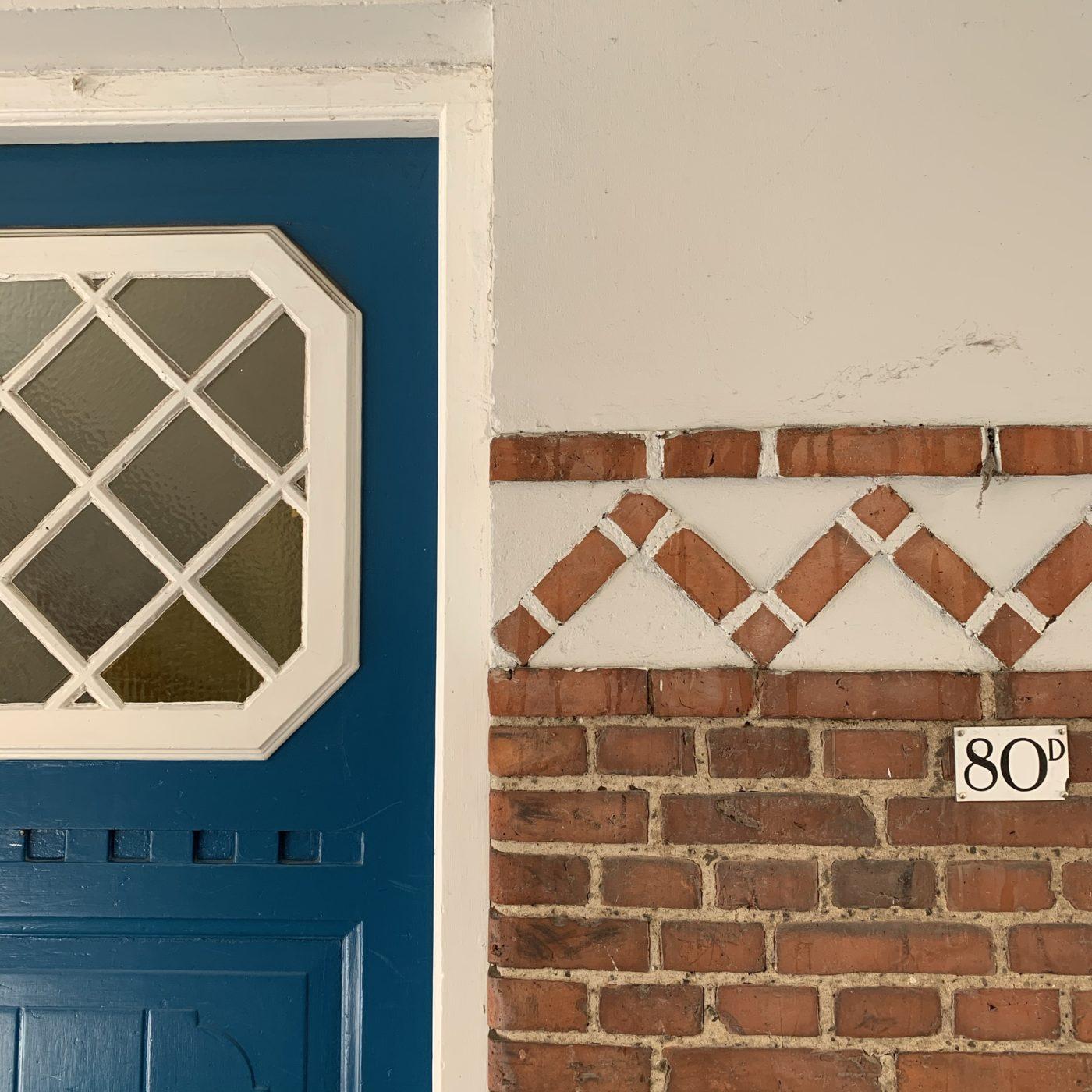 En blå dør med hvidt vindue, i en port med fine dekorative mursten og et skilt med nr. 80D.