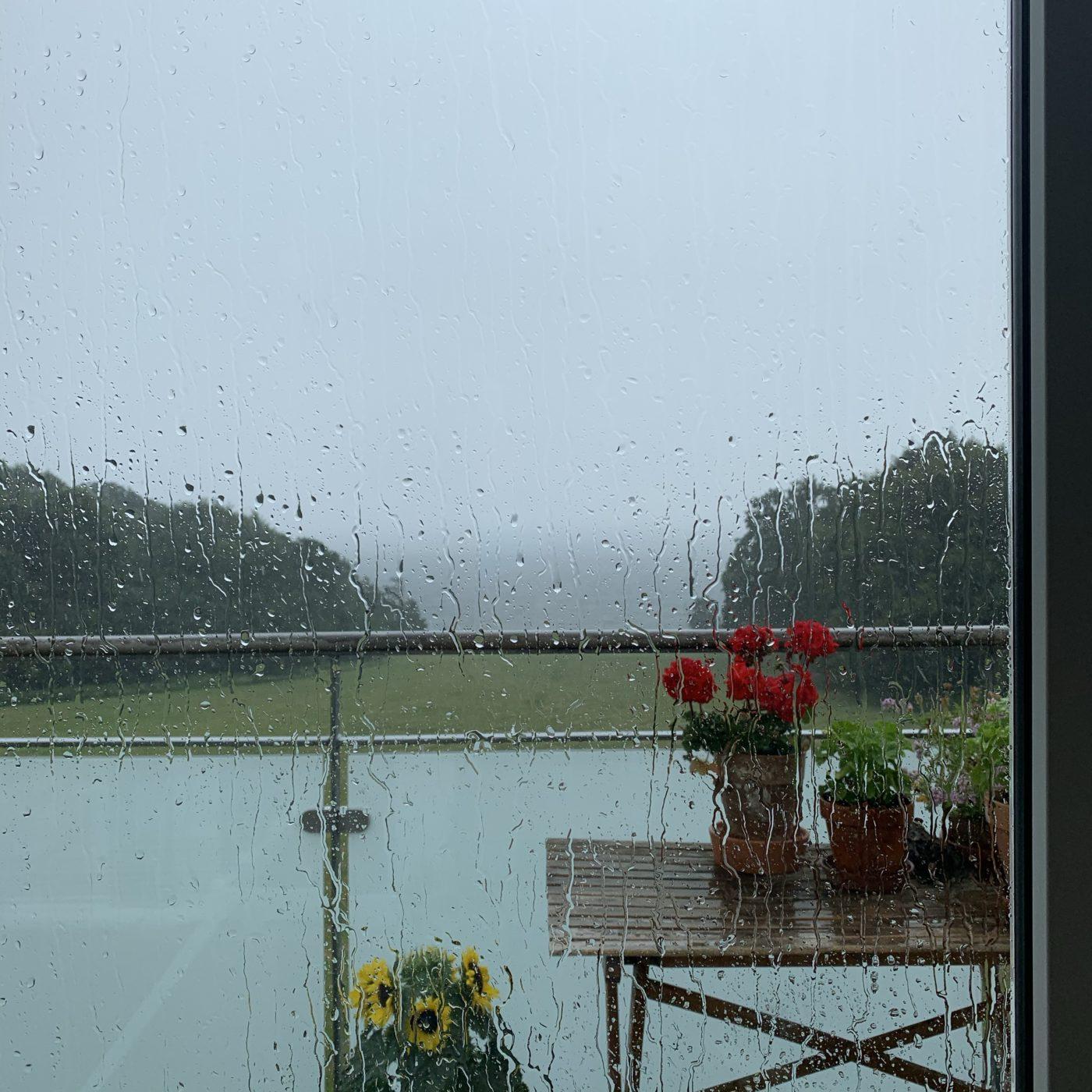 Et kig ud over altanen med potteplanter og masser af regn.