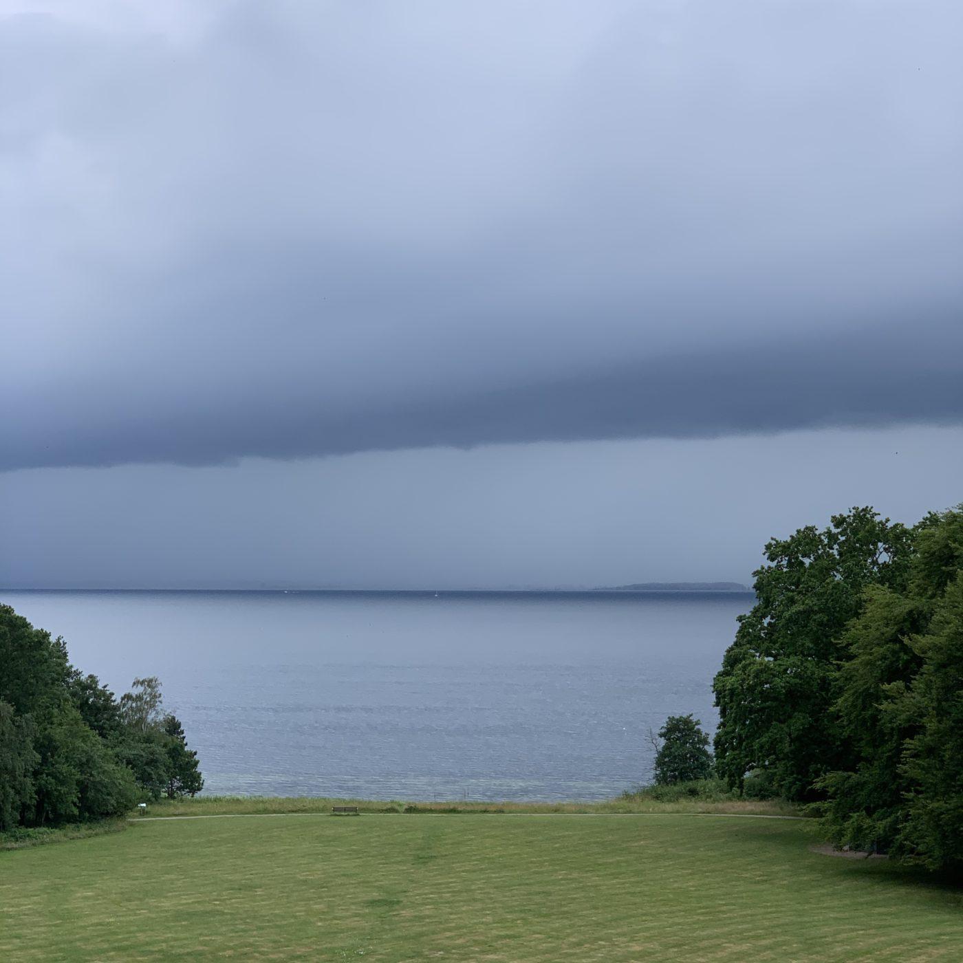 Udsigten fra Vintersbølle Strand ud over Storstrømmen. Grå skyer, gråt vand, grønt græs.